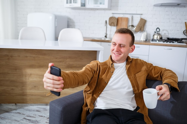 Un jeune homme qui a réussi est assis à la maison sur le canapé avec un téléphone et parle par liaison vidéo. travail à distance pendant le confinement.