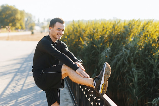 Jeune homme qui s'étend à l'extérieur dans le parc après quelques cercles de course.