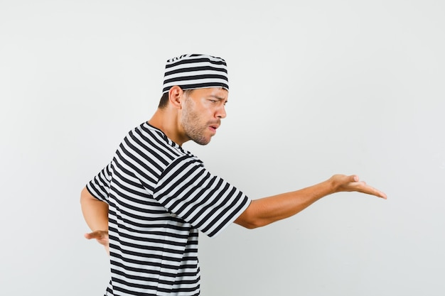 Jeune homme qui s'étend de la main de manière interrogative en chapeau t-shirt rayé et à la colère