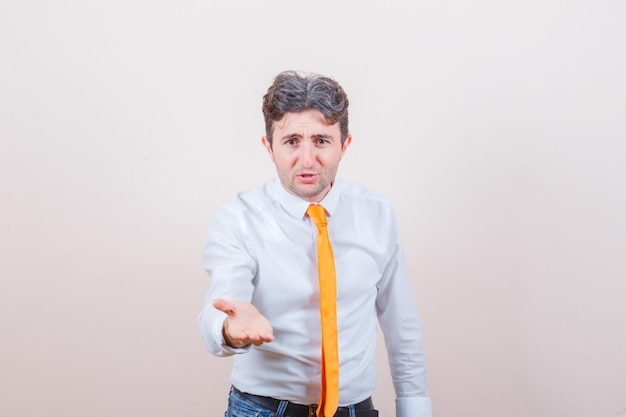Jeune homme qui s'étend de la main de manière interrogative en chemise et jeans
