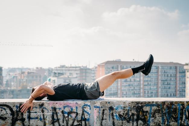 Jeune homme qui s'étend en plein air