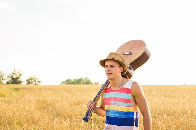 Jeune homme quittant la maison, gars avec guitare marchant au champ de coucher de soleil