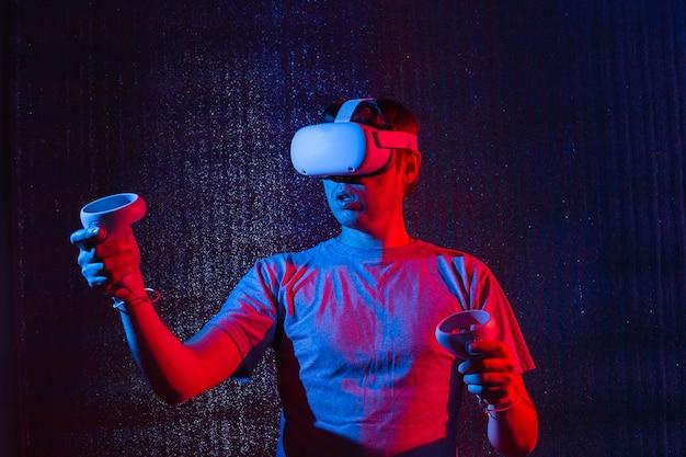 Jeune homme de race blanche de 25 à 30 ans portant un casque de réalité virtuelle et faisant des gestes assis à la lumière du néon. vr, avenir, gadgets, concept technologique.