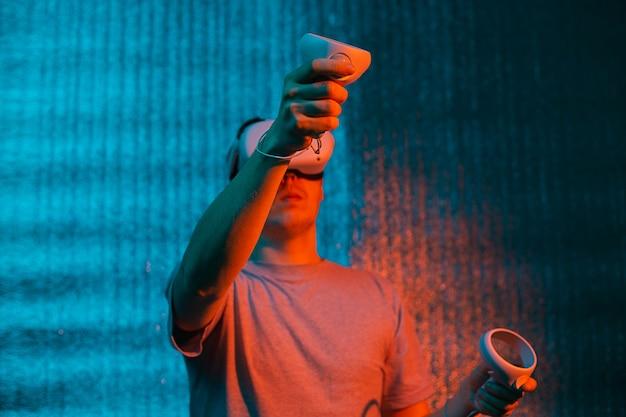 Jeune homme de race blanche de 25 à 30 ans utilisant un casque de réalité virtuelle. vr, avenir, gadgets, concept technologique en néon.