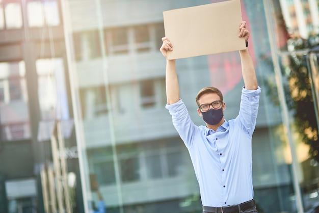 Jeune homme de race blanche activiste portant un masque de protection noir tenant un panneau vide sur le