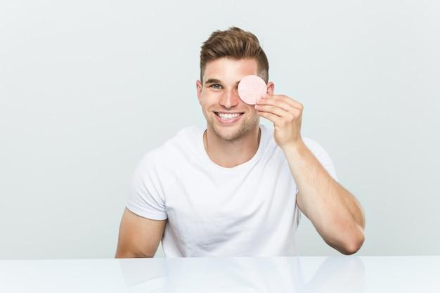 Jeune homme de race blanche à l'aide d'une éponge pour le visage.