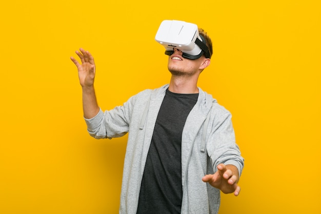 Jeune homme de race blanche à l'aide de lunettes de réalité virtuelle