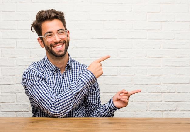 Jeune homme de race blanche assis pointant sur le côté souriant souriant présentant quelque chose