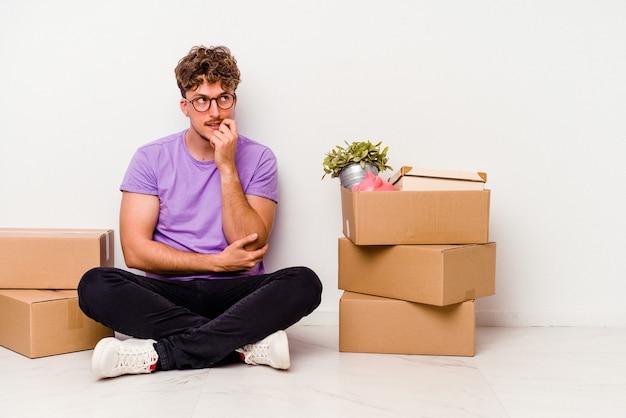 Jeune homme de race blanche assis sur le sol prêt à se déplacer isolé sur fond blanc détendu en pensant à quelque chose en regardant un espace de copie.