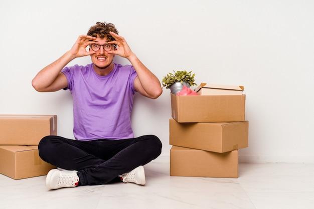 Jeune homme de race blanche assis sur le sol prêt à se déplacer isolé sur fond blanc en gardant les yeux ouverts pour trouver une opportunité de réussite.
