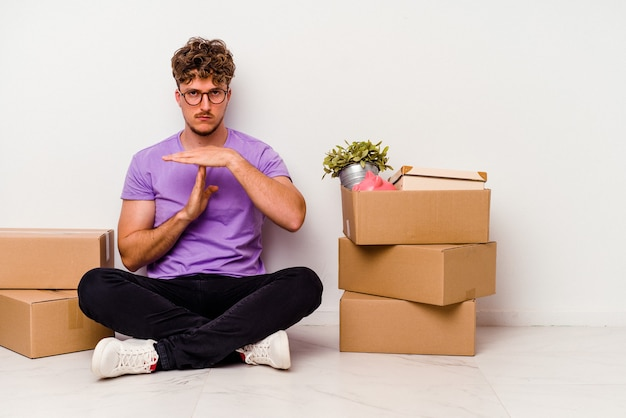 Jeune homme de race blanche assis sur le sol prêt à se déplacer isolé sur fond blanc montrant un geste de temporisation.