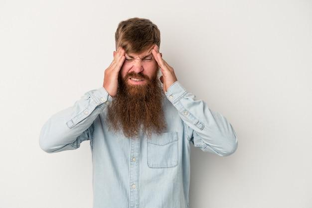 Jeune homme de race blanche au gingembre avec une longue barbe isolé sur fond blanc ayant un mal de tête, touchant le devant du visage.