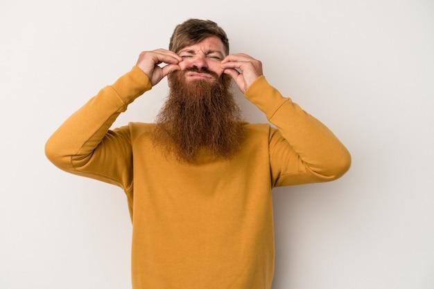 Jeune homme de race blanche au gingembre avec une longue barbe isolé sur fond blanc, doutant entre deux options.