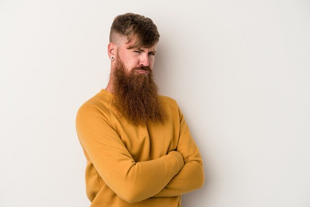 Jeune homme de race blanche au gingembre avec une longue barbe isolé sur fond blanc, fronçant les sourcils de mécontentement, garde les bras croisés.