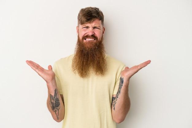 Jeune homme de race blanche au gingembre avec une longue barbe isolé sur fond blanc haussant les épaules confus et douteux pour tenir un espace de copie.