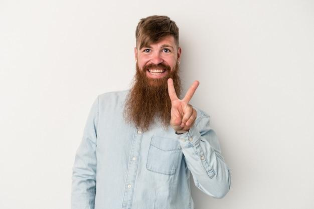 Jeune homme de race blanche au gingembre avec une longue barbe isolé sur fond blanc joyeux et insouciant montrant un symbole de paix avec les doigts.
