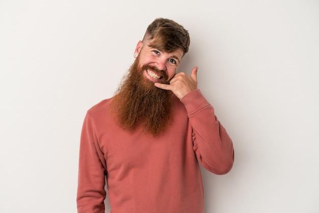 Jeune homme de race blanche au gingembre avec une longue barbe isolé sur fond blanc montrant un geste d'appel de téléphone portable avec les doigts.