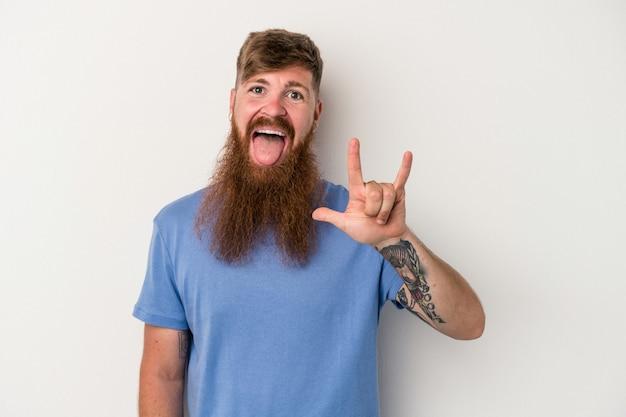 Jeune homme de race blanche au gingembre avec une longue barbe isolé sur fond blanc montrant un geste de cornes comme concept de révolution.