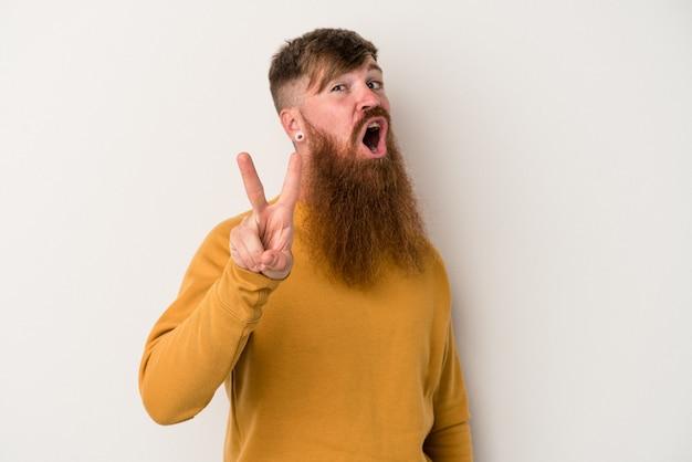 Jeune homme de race blanche au gingembre avec une longue barbe isolé sur fond blanc montrant le numéro deux avec les doigts.