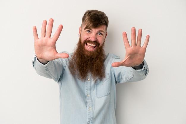 Jeune homme de race blanche au gingembre avec une longue barbe isolé sur fond blanc montrant le numéro dix avec les mains.