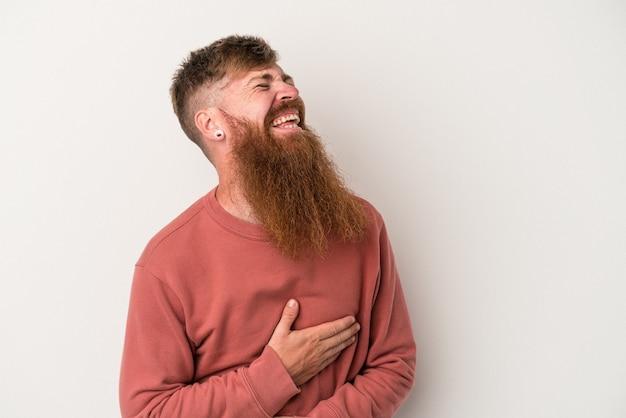 Jeune homme de race blanche au gingembre avec une longue barbe isolé sur fond blanc en riant en gardant les mains sur le cœur, concept de bonheur.