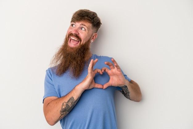 Jeune homme de race blanche au gingembre avec une longue barbe isolé sur fond blanc souriant et montrant une forme de coeur avec les mains.