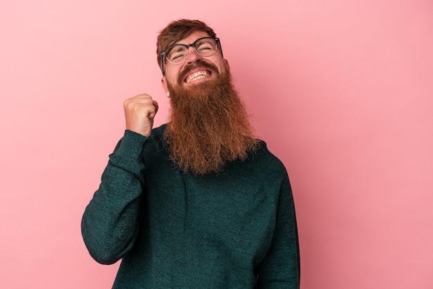 Jeune homme de race blanche au gingembre avec une longue barbe isolé sur fond rose célébrant une victoire, une passion et un enthousiasme, une expression heureuse.