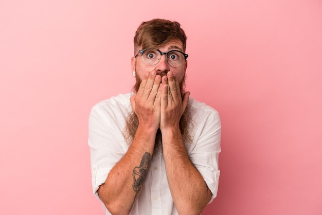 Jeune homme de race blanche au gingembre avec une longue barbe isolé sur fond rose choqué couvrant la bouche avec les mains.