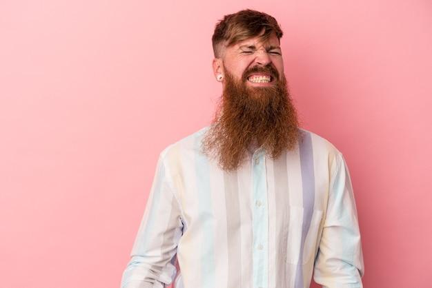 Jeune homme de race blanche au gingembre avec une longue barbe isolé sur fond rose dansant et s'amusant.