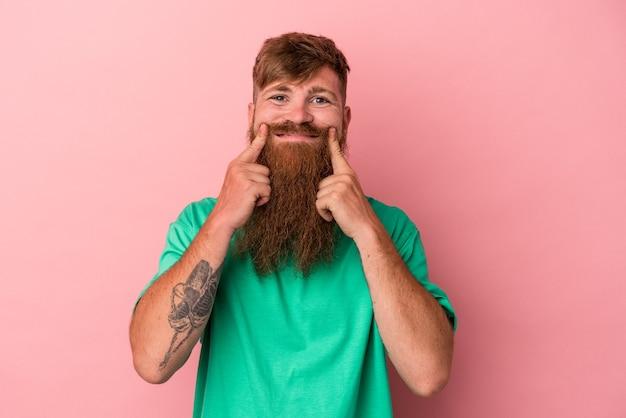 Jeune homme de race blanche au gingembre avec une longue barbe isolé sur fond rose, doutant entre deux options.