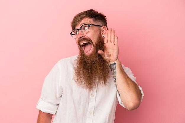 Jeune homme de race blanche au gingembre avec une longue barbe isolé sur fond rose essayant d'écouter un potin.