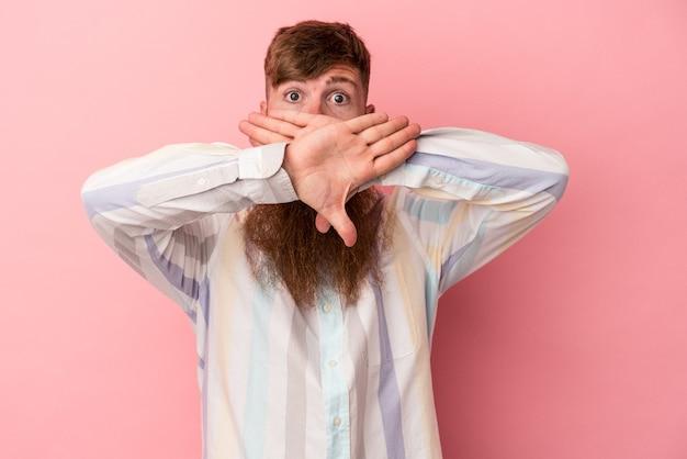 Jeune homme de race blanche au gingembre avec une longue barbe isolé sur fond rose faisant un geste de déni