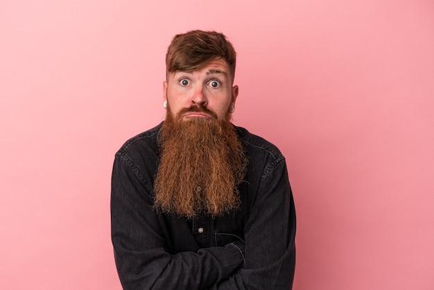 Jeune homme de race blanche au gingembre avec une longue barbe isolé sur fond rose hausse les épaules et ouvre les yeux confus.