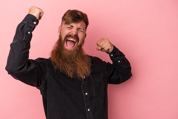 Jeune homme de race blanche au gingembre avec une longue barbe isolé sur fond rose levant le poing après une victoire, concept gagnant.