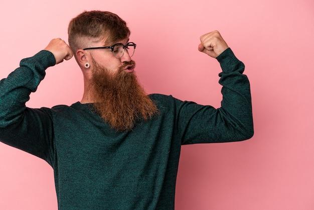Jeune homme de race blanche au gingembre avec une longue barbe isolé sur fond rose montrant un geste de force avec les bras, symbole du pouvoir féminin
