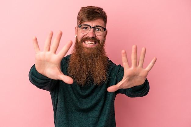 Jeune homme de race blanche au gingembre avec une longue barbe isolé sur fond rose montrant le numéro dix avec les mains.