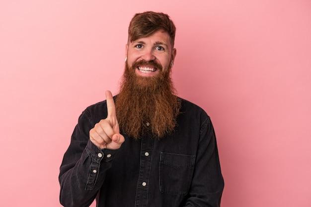 Jeune homme de race blanche au gingembre avec une longue barbe isolé sur fond rose montrant le numéro un avec le doigt.