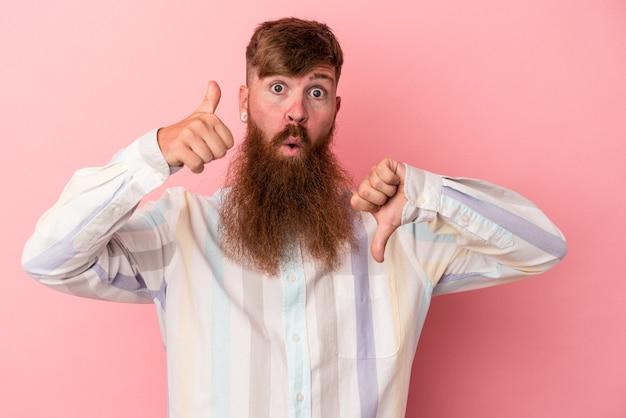 Jeune homme de race blanche au gingembre avec une longue barbe isolé sur fond rose montrant les pouces vers le haut et les pouces vers le bas, concept de choix difficile