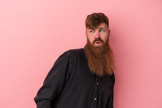 Jeune homme de race blanche au gingembre avec une longue barbe isolé sur fond rose regarde de côté souriant, joyeux et agréable.