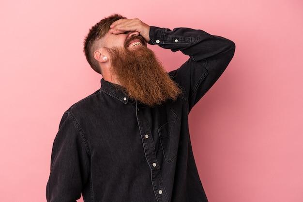 Jeune homme de race blanche au gingembre avec une longue barbe isolé sur fond rose rit joyeusement en gardant les mains sur la tête. notion de bonheur.