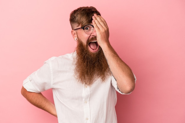 Jeune homme de race blanche au gingembre avec une longue barbe isolé sur fond rose s'amusant à couvrir la moitié du visage avec la paume.