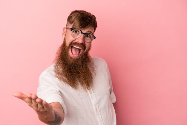 Jeune homme de race blanche au gingembre avec une longue barbe isolé sur fond rose s'étendant la main à la caméra en geste de salutation.