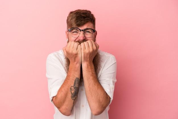 Jeune homme de race blanche au gingembre avec une longue barbe isolé sur fond rose se rongeant les ongles, nerveux et très anxieux.