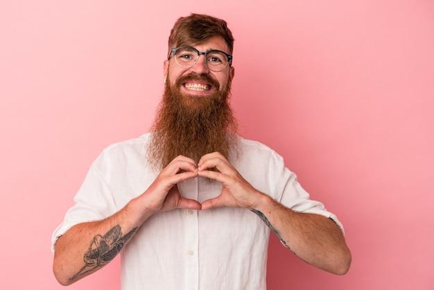Jeune homme de race blanche au gingembre avec une longue barbe isolé sur fond rose souriant et montrant une forme de coeur avec les mains.