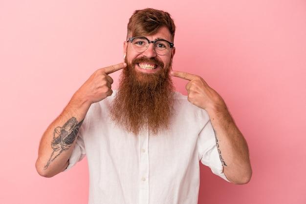 Jeune homme de race blanche au gingembre avec une longue barbe isolé sur fond rose sourit, pointant du doigt la bouche.