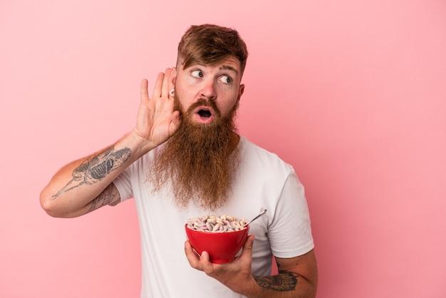 Jeune homme de race blanche au gingembre avec une longue barbe tenant un bol de céréales isolé sur fond rose essayant d'écouter un potin.