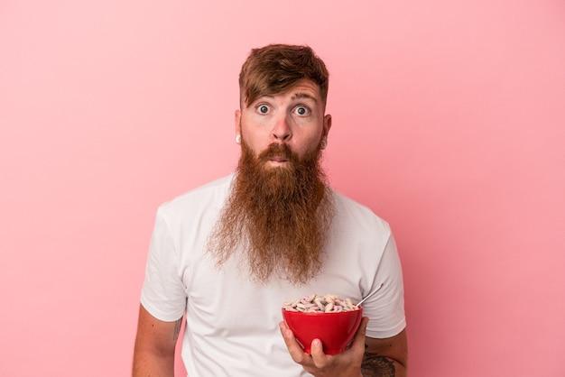 Jeune homme de race blanche au gingembre avec une longue barbe tenant un bol de céréales isolé sur fond rose hausse les épaules et ouvre les yeux confus.