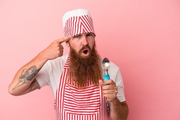 Jeune homme de race blanche au gingembre avec une longue barbe tenant une boule isolée sur fond rose montrant un geste de déception avec l'index.