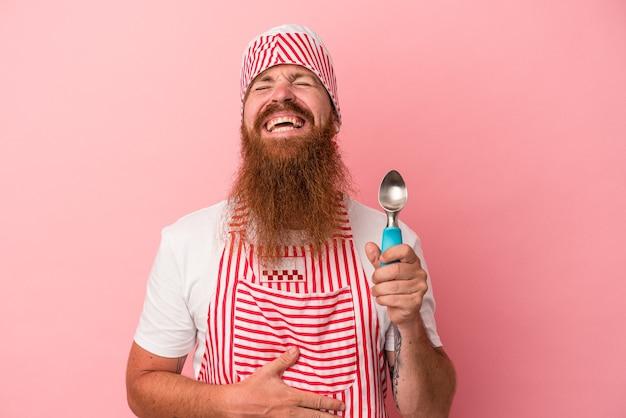 Jeune homme de race blanche au gingembre avec une longue barbe tenant une boule isolée sur fond rose rit fort en gardant la main sur la poitrine.