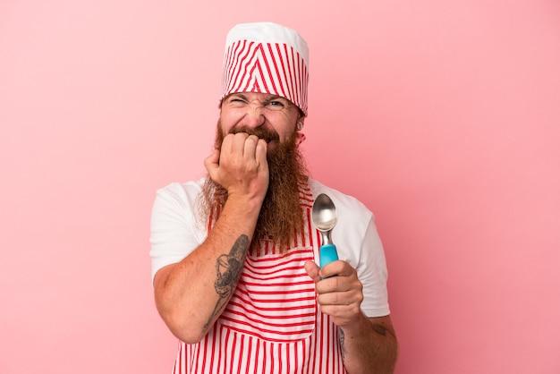 Jeune homme de race blanche au gingembre avec une longue barbe tenant une boule isolée sur fond rose se rongeant les ongles, nerveux et très anxieux.